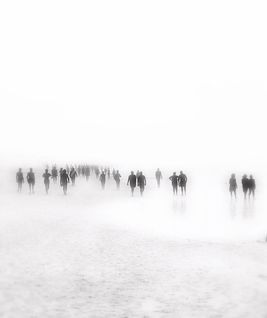 Menschen im Nebel am Strand